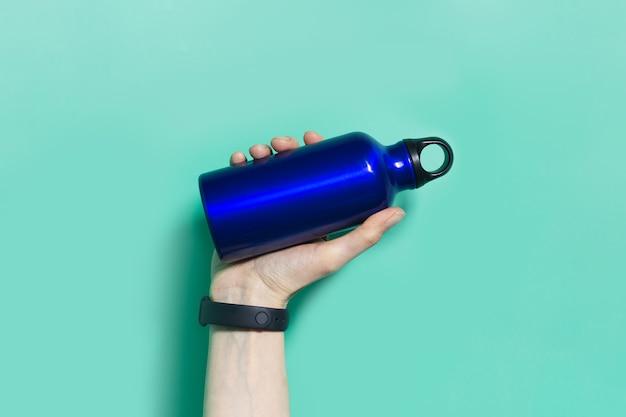 Close-up of female hand holding a réutilisable eco, bouteille d'eau thermo de couleur bleu fantôme, isolé sur aqua menthe