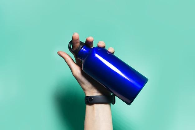 Close-up of female hand holding a réutilisable eco, bouteille d'eau thermo en métal de couleur bleu fantôme, isolé sur aqua menthe