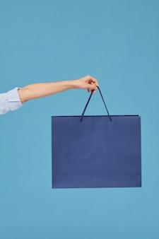 Close-up of female hand holding sac en papier isolé sur fond bleu
