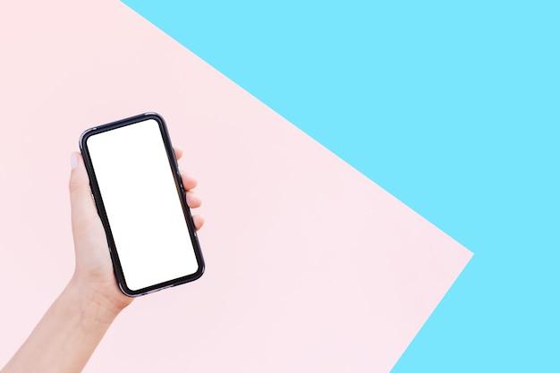 Close-up of female hand holding smartphone avec maquette sur des surfaces de rose pastel et bleu de couleurs