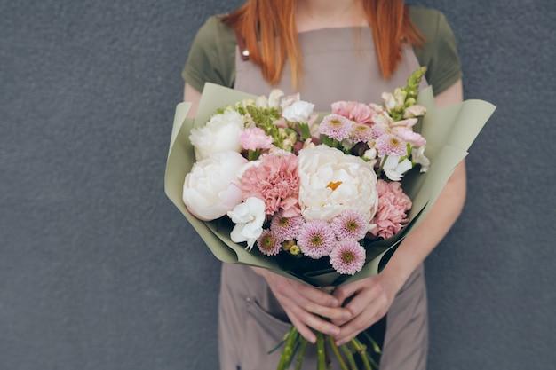 Close-up of fleuriste méconnaissable en tablier debout contre un mur gris et tenant un bouquet tendre lumineux en papier kraft vert