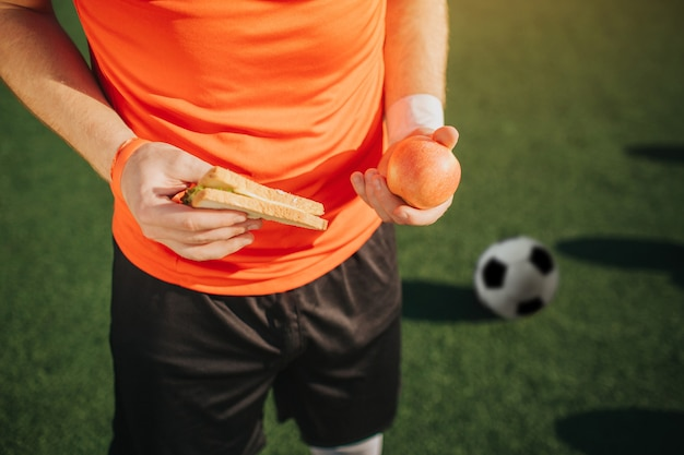Close up of football plaueer holding apple et sandwich dans les mains