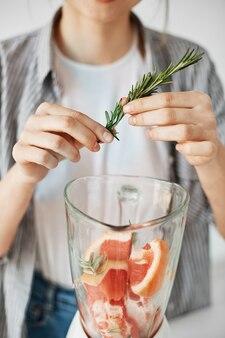 Close up of girl blending smoothie sain de pamplemousse detox ajoutant le romarin.