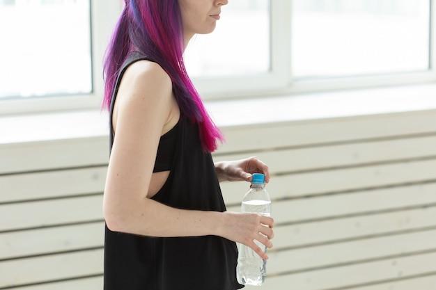 Close up of girl hipster aux cheveux colorés boit de l'eau d'une bouteille après un entraînement physique intense