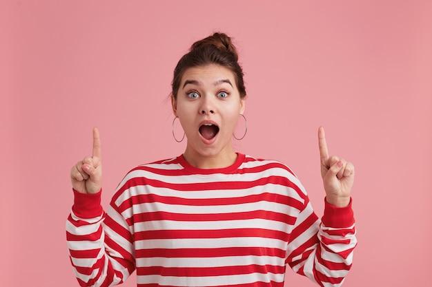 Close up of happy femme étonnée avec des taches de rousseur, portant des manches longues rayées, avec la bouche grande ouverte et les doigts levant et pointant vers le haut à la surface
