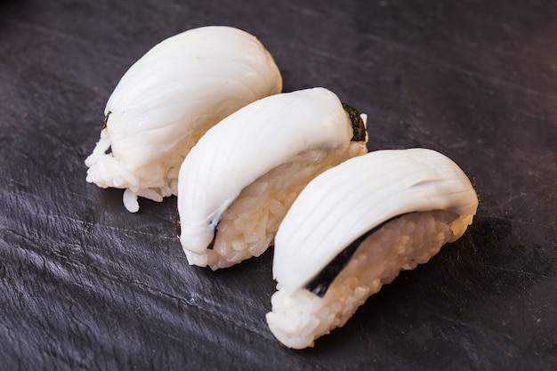 Close-up of ica sushi avec calmar sur fond d'ardoise noire