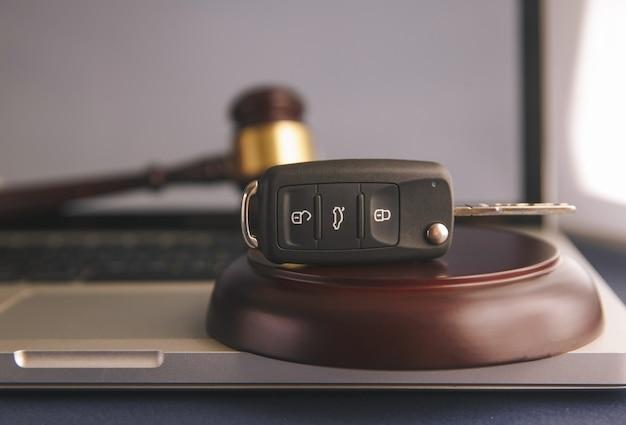 Close up of juge marteau et clés de voiture sur table d'harmonie sur fond blanc