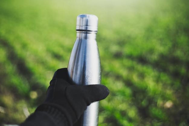 Close-up of male hand habillé en gant tenant une bouteille d'eau thermo en acier réutilisable sur le mur d'herbe verte floue.