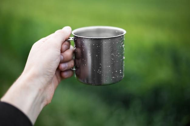Close-up of male hand holding tasse en acier pulvérisé avec de l'eau
