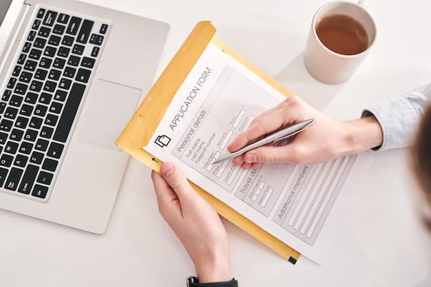 Close-up of manager méconnaissable assis au bureau avec tasse de thé et ordinateur portable et remplir le formulaire de demande reçu par courrier