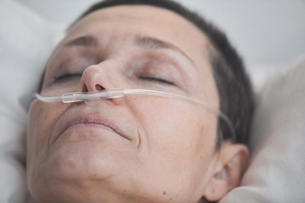 Close-up of mature patient allongé les yeux fermés sous compte-gouttes à l'hôpital