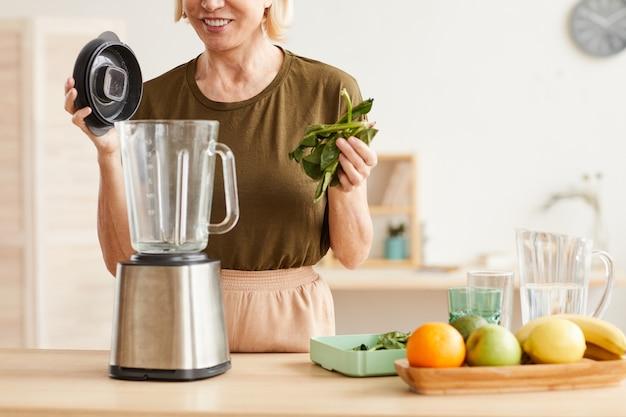 Close-up of mature woman putting épinards dans le mélangeur, elle va faire un cocktail sain
