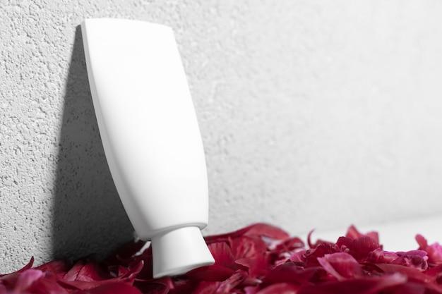Close-up of modern tube cosmétique debout sur le bureau avec des pétales de fleurs roses