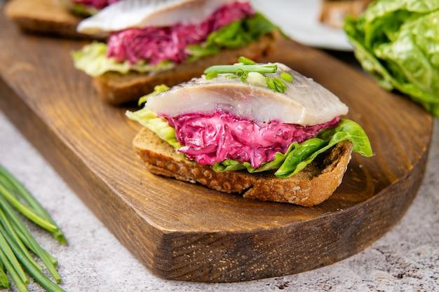 Close up of sandwich au hareng avec betterave et salade verte sur planche de bois