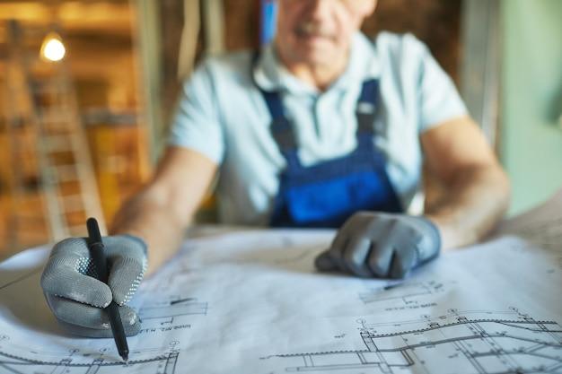 Close up of senior construction worker regardant les plans d'étage lors de la rénovation de la maison, copiez l'espace
