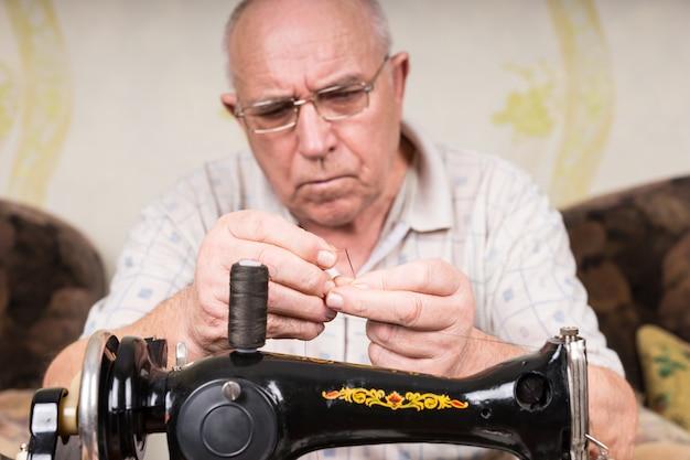 Close up of senior man en concentration profonde de l'aiguille de filetage de la machine à coudre manuelle à l'ancienne