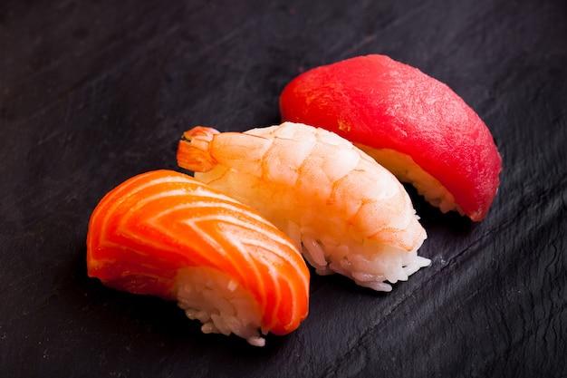 Close-up of set of tree sushi avec saumon, thon et crevettes sur fond noir