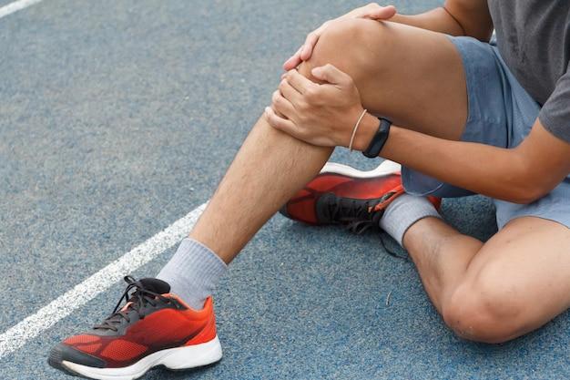 Close up of sport man souffrant de douleur sur le sport en cours d'exécution blessure au genou après avoir exécuté. blessure du concept d'entraînement.