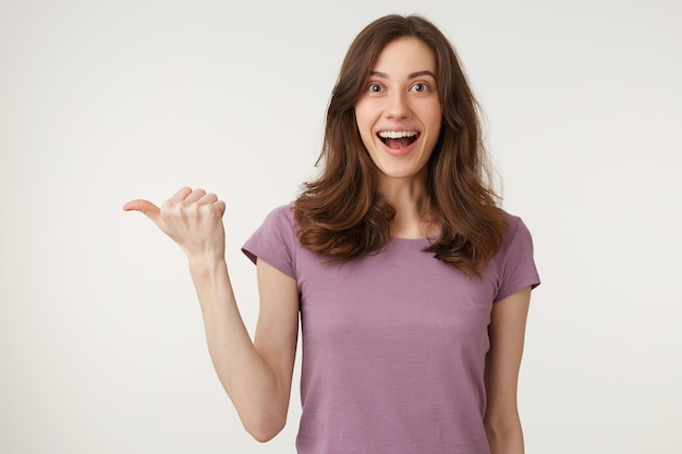 Close up of surpris séduisant adolescent en t-shirt pointant de côté avec la mâchoire tombée