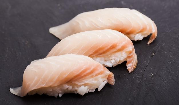 Close-up of tai nigiri sushi sur fond d'ardoise noire