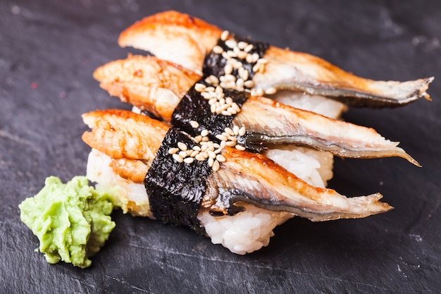 Close-up of unagi sushi avec anguille et wasabi sur fond d'ardoise noire