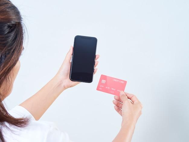 Close-up of woman hold téléphone mobile, écran vide et carte bancaire de crédit sur fond gris