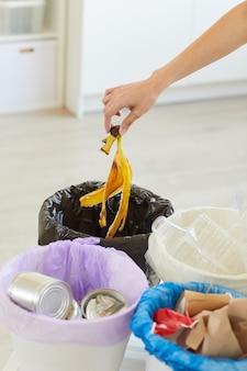 Close-up of woman putting plastique, papier, autres déchets dans les poubelles bio dans la cuisine