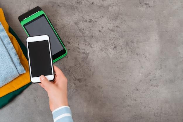Close up of woman's hand holding mobile phone près du terminal de paiement, effectuant le paiement sans contact pour l'achat en magasin de vêtements