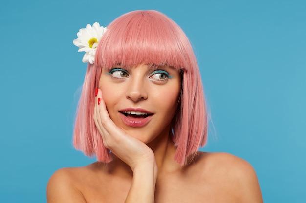 Close-up of young beautiful female avec courte coupe de cheveux rose penchant son menton sur la main levée tout en regardant positivement de côté avec un sourire léger, isolé sur fond bleu