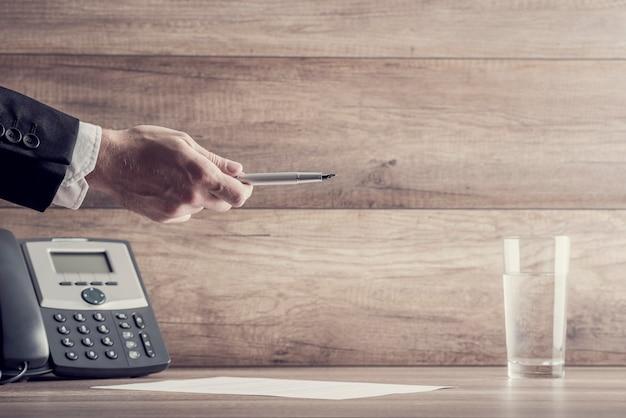 Close up on hand holding pen sur papier comme symbole du contrat commercial ou du concept de clôture des ventes