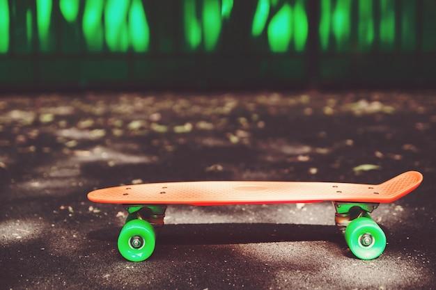 Close up orange penny skateboard sur l'asphalte derrière le mur vert