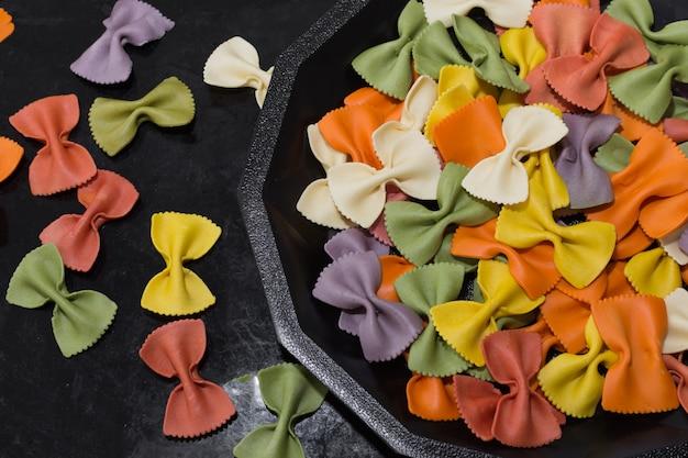 Close-up de pâtes farfalle multicolores brutes italiennes sur fond noir.
