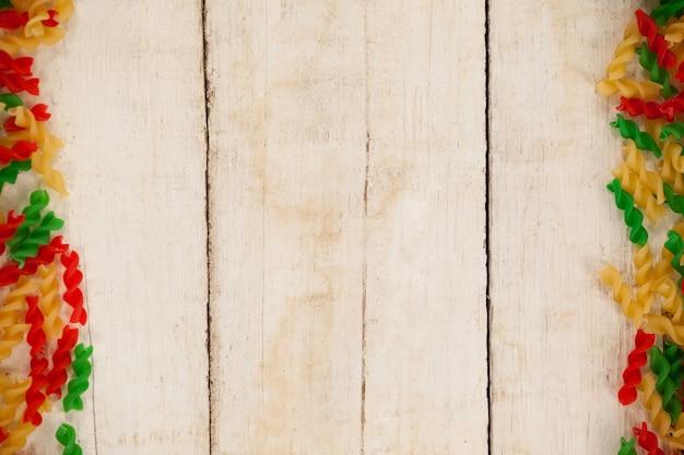 Close-up de pâtes rotini tricolores sur une surface en bois