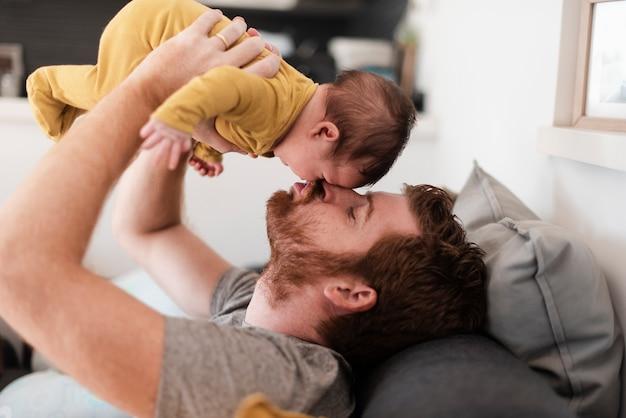 Close-up père assis sur le canapé avec bébé