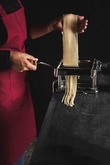 Close-up personne faisant des pâtes avec un fond sombre