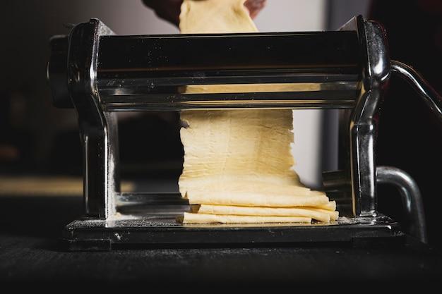 Close-up personne faisant des pâtes avec machine