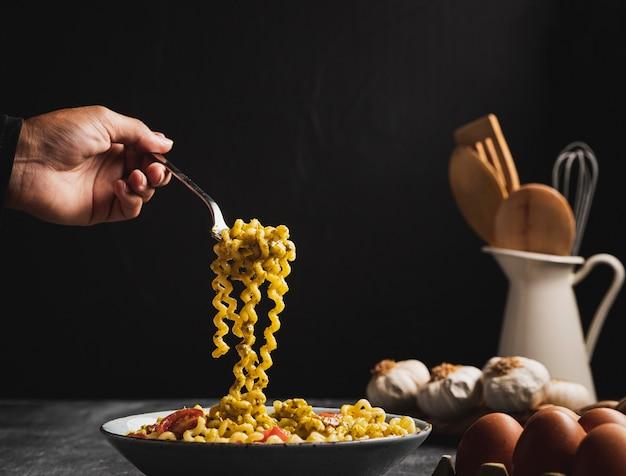 Close-up personne tenant des pâtes frisées avec une fourchette