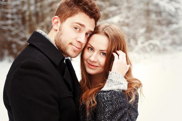 Close-up d'un petit ami fier embrassant sa petite amie sur une journée froide