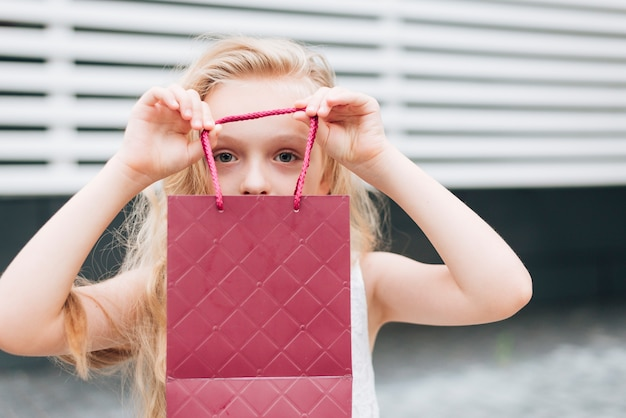 Close-up petite fille tenant un sac cadeau