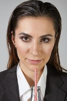 Close up photo verticale de jolie femme de race blanche heureuse avec les cheveux mouillés peignés en arrière et se maquiller posant à l'intérieur avec une bouteille en verre de boisson gazeuse sucrée froide, se rafraîchissant sur la journée de travail