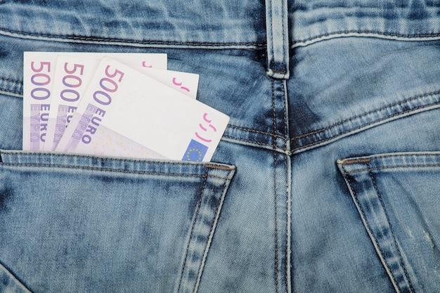 Close up plusieurs cinq cents billets en papier-monnaie euro dans la poche arrière de jeans, low angle view
