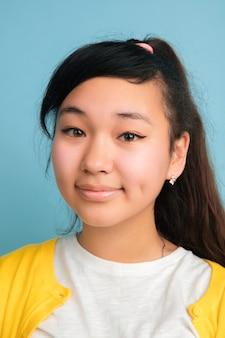 Close up portrait de l'adolescent asiatique isolé sur studio bleu