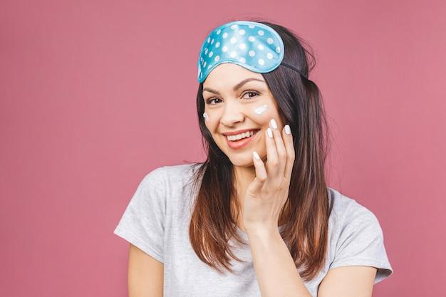 Close up portrait de beauté d'une belle femme riante en masque de sommeil, appliquer la crème pour le visage et regarder ailleurs