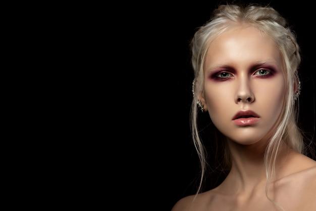 Close up portrait de beauté de jeune femme aux yeux charbonneux rouges sur fond noir