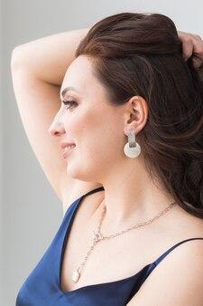 Close-up portrait de la belle jeune femme avec une coiffure élégante et des bijoux de luxe et