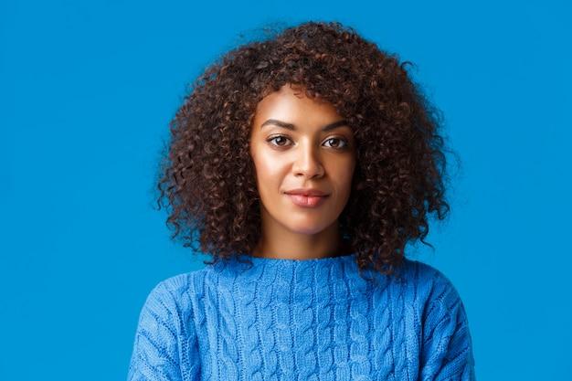Close-up portrait calme et insouciant beau femme afro-américaine en pull, avec une coiffure frisée afro, souriant mignon et regardant la caméra avec une expression agréable et agréable, bleu