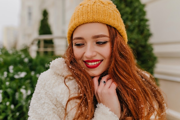 Close-up portrait de charmante femme au gingembre debout près de sapin. photo extérieure d'une fille souriante joyeuse au chapeau d'hiver.