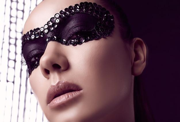 Close-up portrait de charmante femme brune élégante en masque de paillettes posant sur fond noir