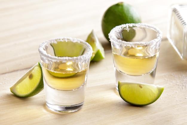 Close up portrait de deux coups de tequila avec tranche de citron vert et sel sur table en bois