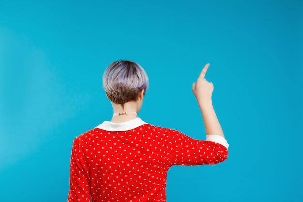 Close up portrait de dos belle fille de poupée avec de courts cheveux violet clair portant une robe rouge pointant avec le doigt sur le mur bleu